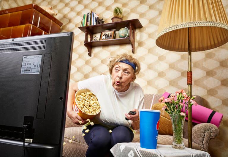 ältere Dame sitzt vor einem Fernseher mit Popcorn