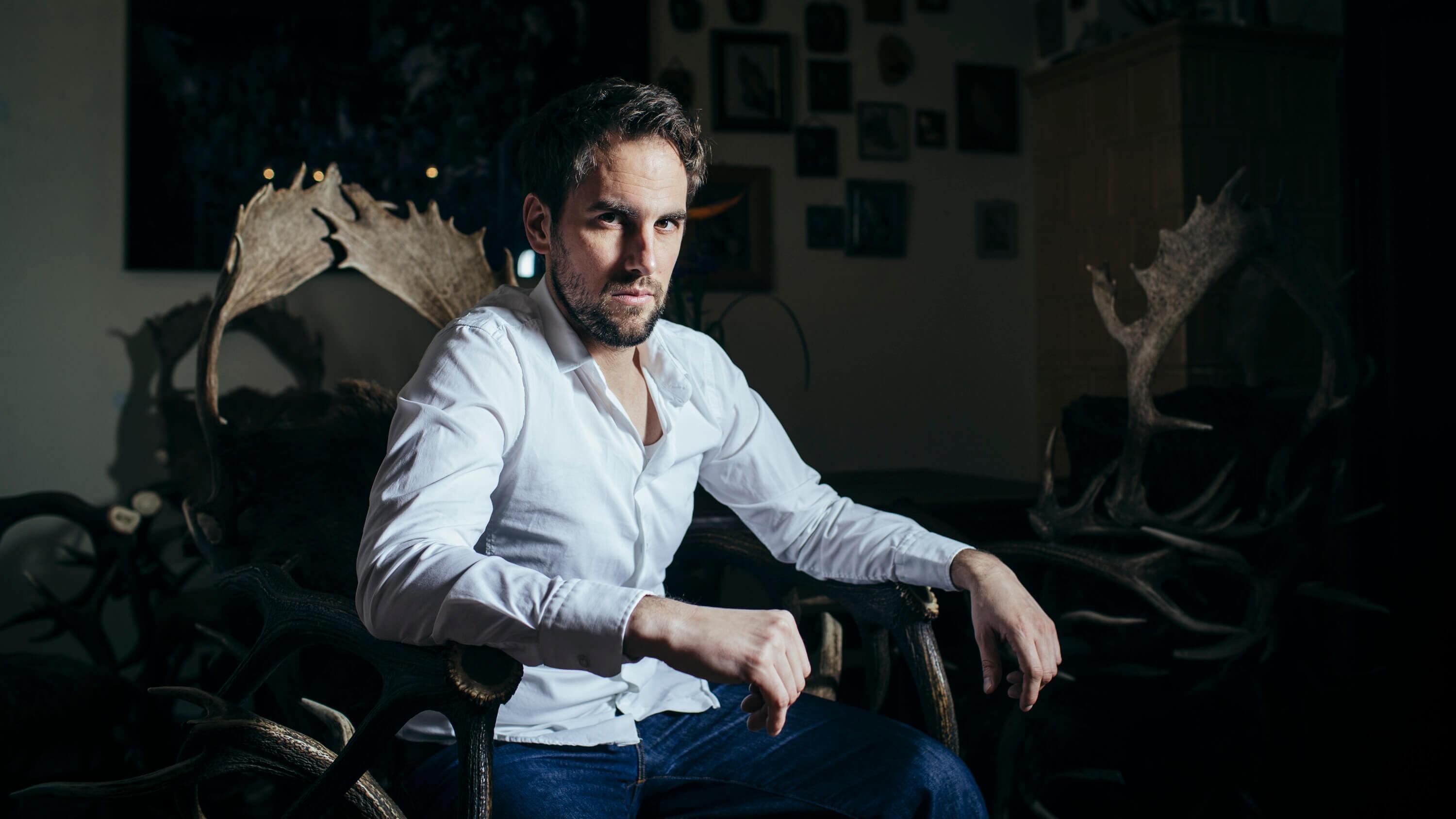 Jan Hasenfuss, Schauspieler, sitzt auf Hirschsessel