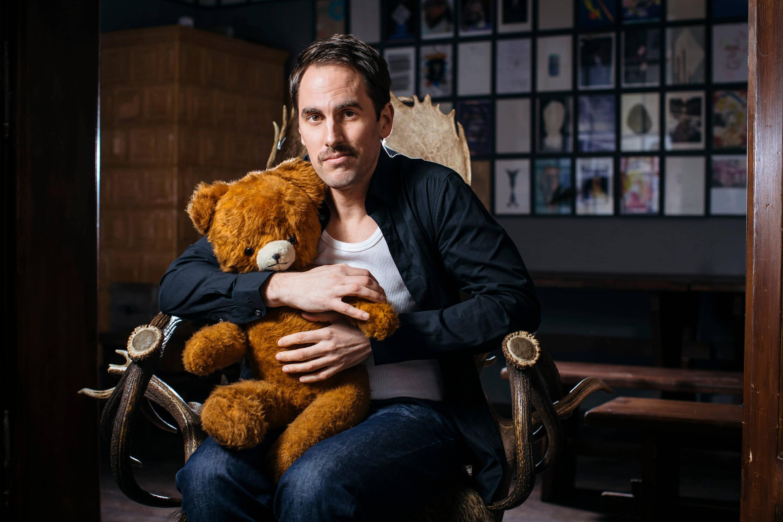 Jan Hasenfuss, Schauspieler, mit Teddy auf Hirschsessel